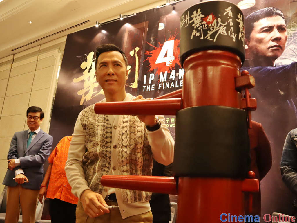 Donnie Yen poses with a wooden dummy after signing it.